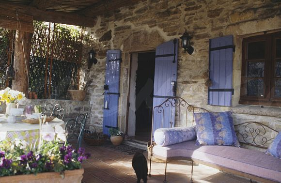 Image: Blue cushions on wrought iron day bed on veranda of