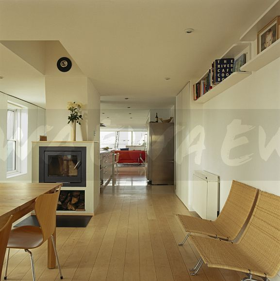 Mid Century Modern Furniture In Open Plan Loft Conversion Dining Area With Wood Burning Stove And Wooden Flooring