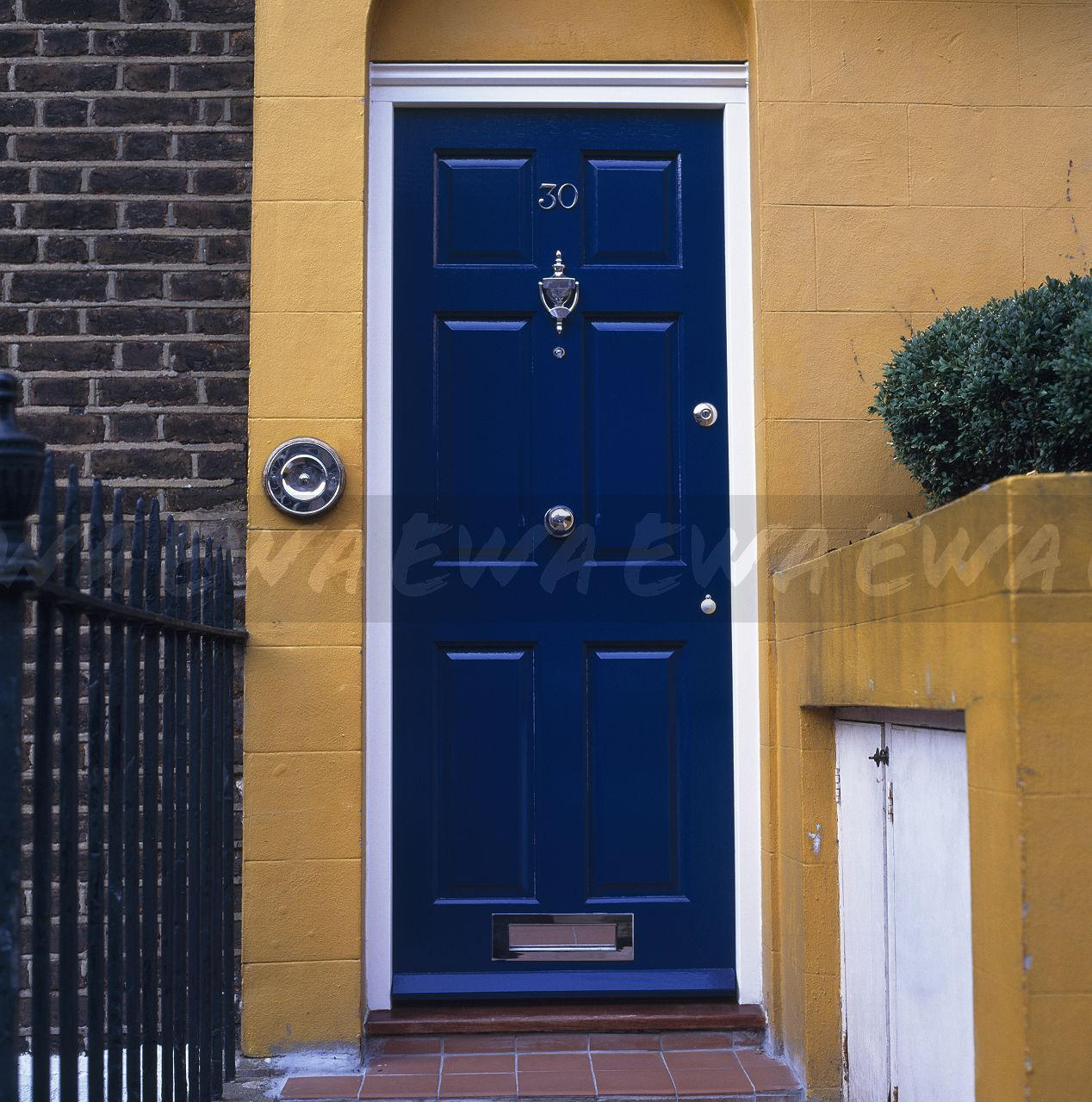 Close Up Of Blue Front Door On Traditional Dark Yellow House