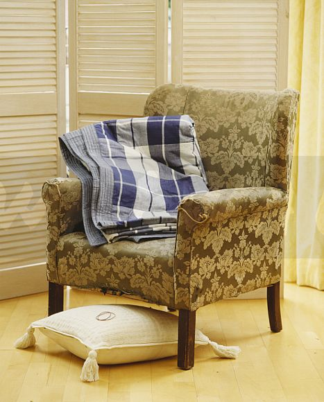 Close Up Of Folded Blue Checked Fabric Throw On Old Armchair In Front Of  Louvred Screen Before And After Showing How To Wrap An Old Chair