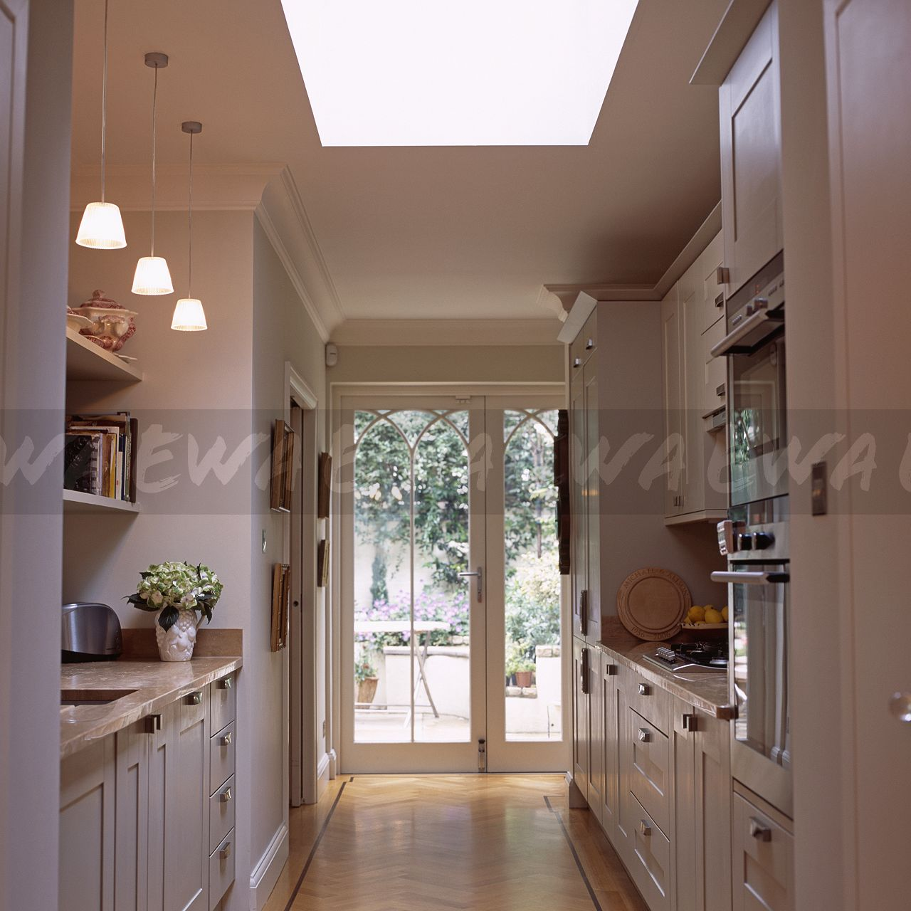 Image: Pendant Lights In White Galley Kitchen Extension With Patio Doors