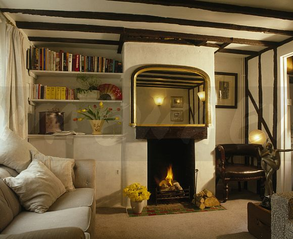 Image: Large Mirror Above Small Fireplace In Cottage