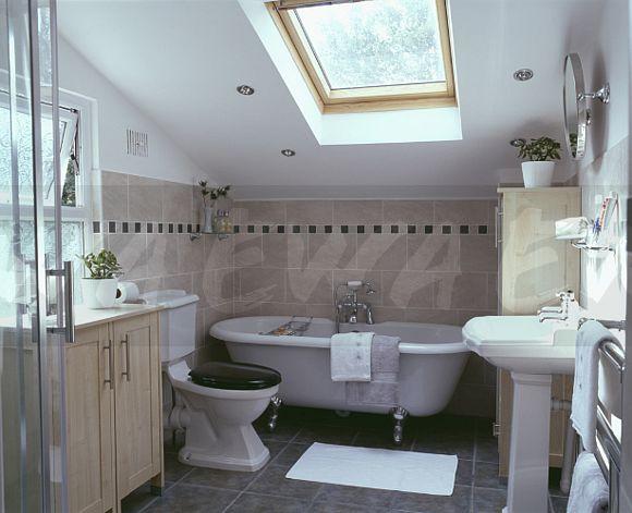 Roll Top Bath Below Velux Window In Modern Loft Conversion Bathroom With Beige Wall Tiles