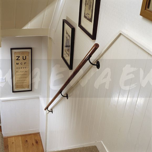Wooden Handrail On Tongue+groove Panelled Wall Of Cream Staircase
