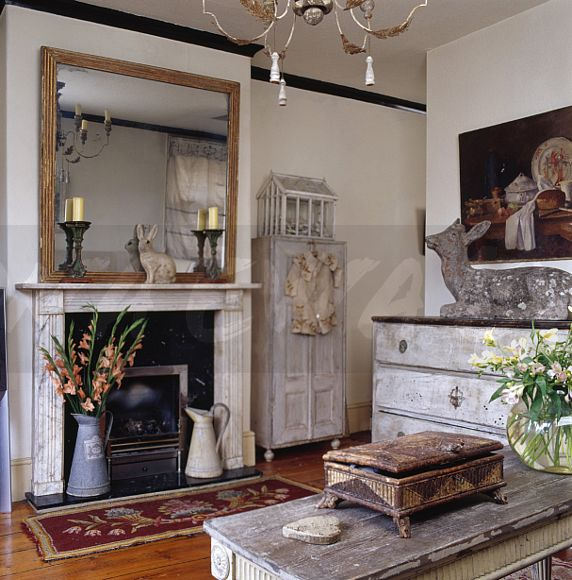 Large Mirror Above Marble Fireplace In Country Living Room With Distressed  Painted Furniture