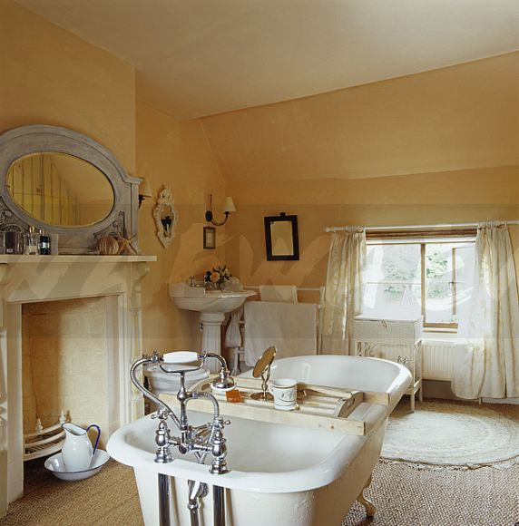 Image: Roll-top bath with wooden bath-rack in centre of country ...