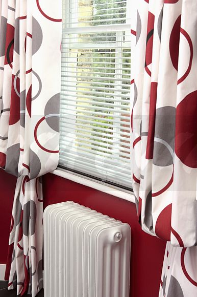 Close Up Of White Slatted Blind And Red Patterned Curtains On Window Above Radiator