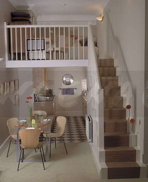 Small living area on mezzanine above kitchen and modern chairs in dining  room beside stairs in