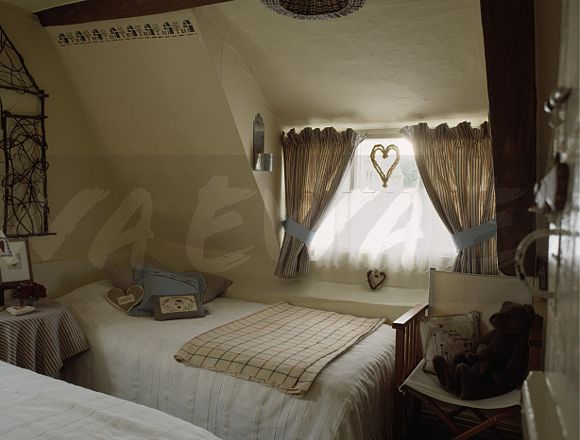 Striped curtains and heart ornament on window in attic bedroom with white covers on twin beds & Image: Striped curtains and heart ornament on window in attic ...
