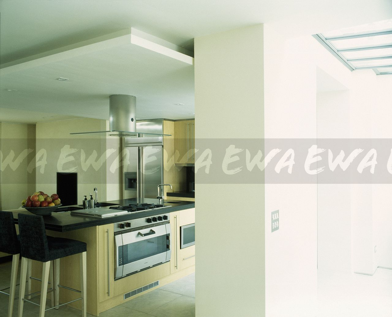 Black Stools At Breakfast Bar On Island Unit With False Ceiling And Extractor Above Oven