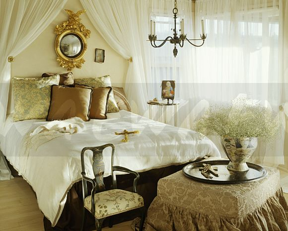 Antique Gilt Mirror And White Voile Drapes Above Bed With Silk Cushions And  White Quilt In Bedroom With White Voile Curtains