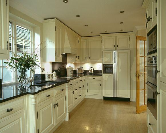 Laminated Wood Flooring In Kitchen With Black Granite Worktops On White Units And Large Fridge Freezer