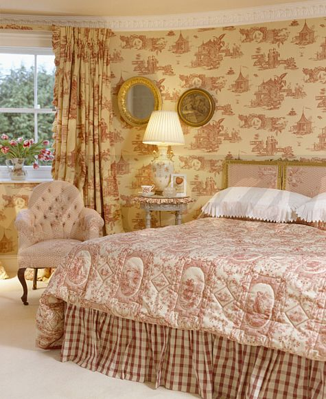 Red+white Toile De Jouy Wallpaper In Bedroom With Pink+white Quilt On Bed  And Lighted Lamp On Bedside Table