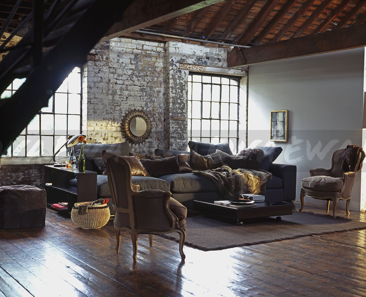 Superbe French Style Armchairs And Wooden Flooring In Loft Conversion Living Room  With Large Sofa Piled With Cushions