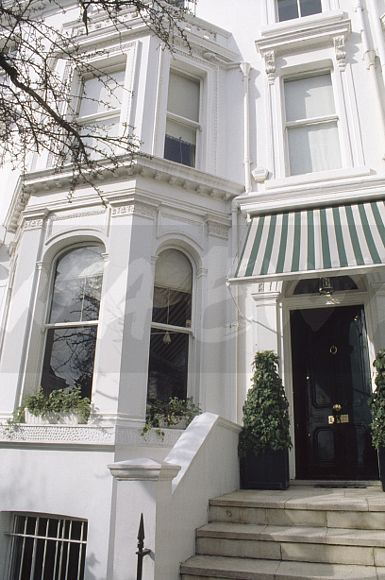 Striped Awning Above Black Front Door In Large White Victorian Terraced  House In London