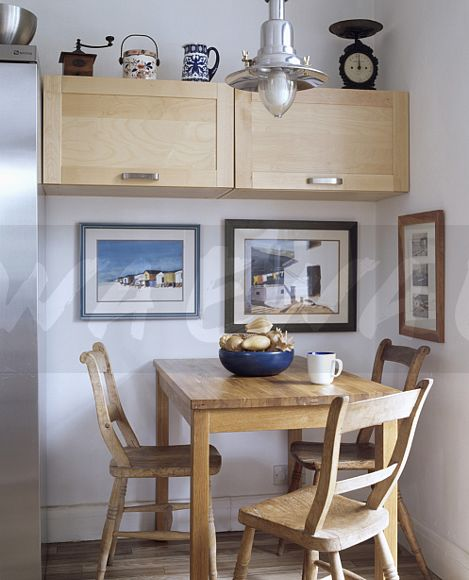 Small Pale Wood Fitted Cupboard And Pictures On Wall In Dining Area With  Plain Wood Table And Chairs
