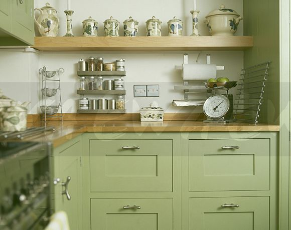 Pottery Jars On Beech Shelf Above Pastel Green Kitchen Units