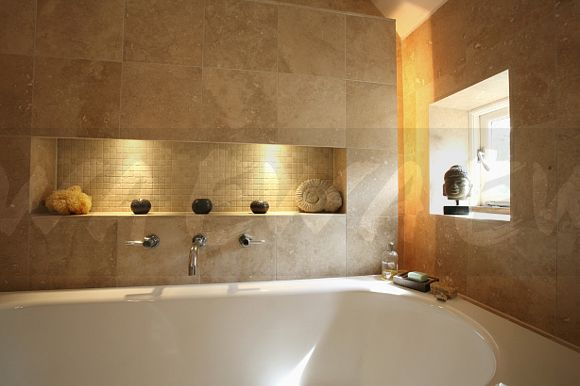 Image: Lighted alcove in limestone tiled wall above bath in modern ...