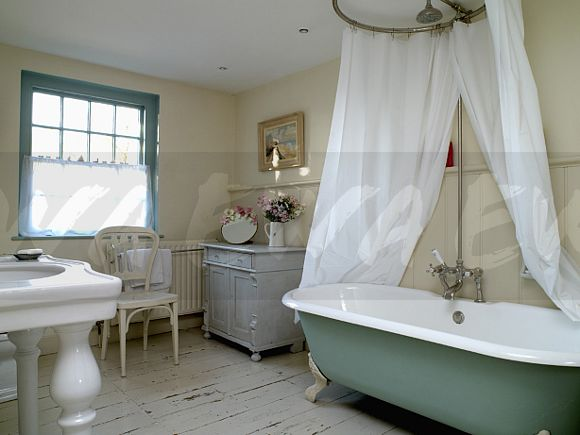 Image: White shower curtains on circular ring above green rolltop ...