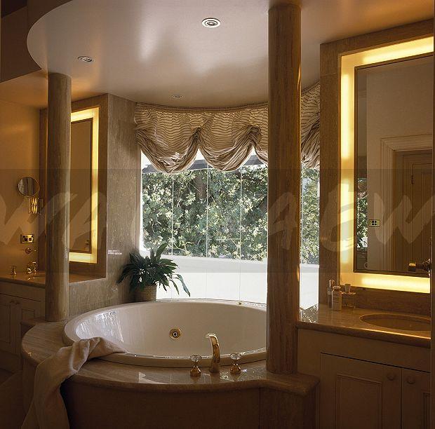 Image: Striped festoon blind above spa bath in nineties bathroom ...
