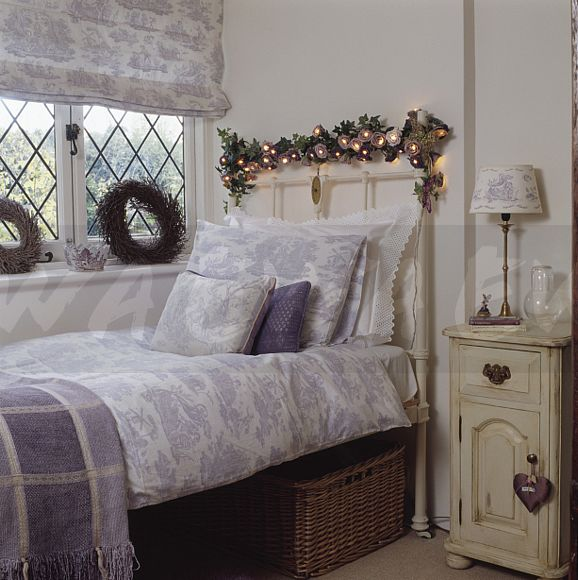 Image Lighted Garland Above White Cast Iron Bed With