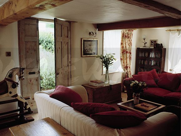Image: Red sofa in cottage living room with red cushions ...