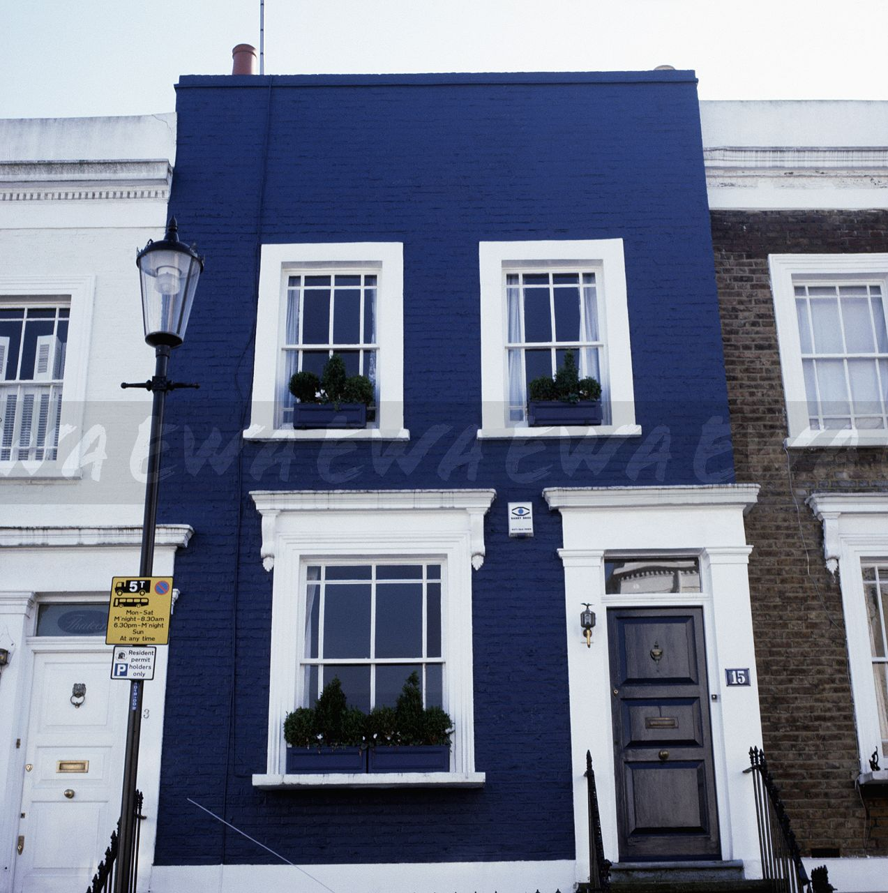White-painted window and door frmes of dark blue traditional terraced ...: https://www.ewastock.com/image/65260