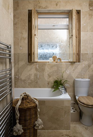 Image Folding Wooden Shutters On Frosted Glass Window Above Bath In Travertine Tiled Bathroom