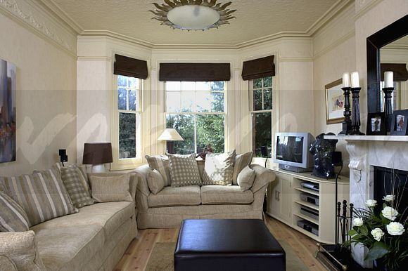 image beige sofas in cream living room with black blinds on bay