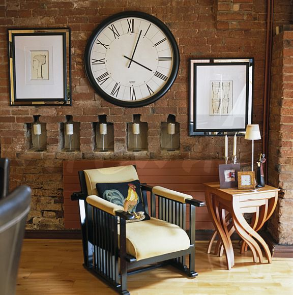 large clock on brick wall with candles in small alcoves in living room